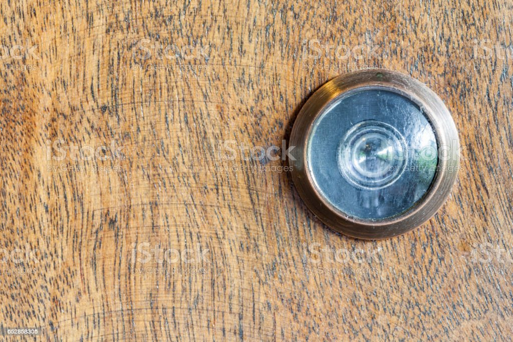 Detail of old lens peephole on wooden door background. stock photo