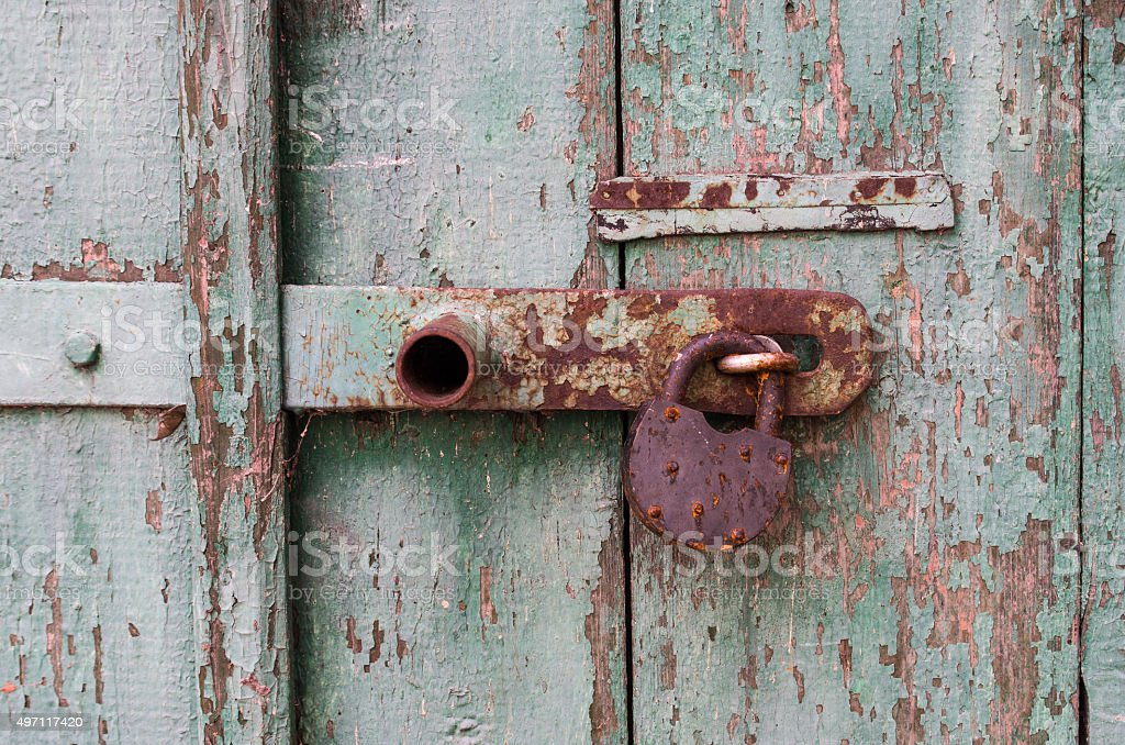 Detail of old wooden door with rusty padlock stock photo