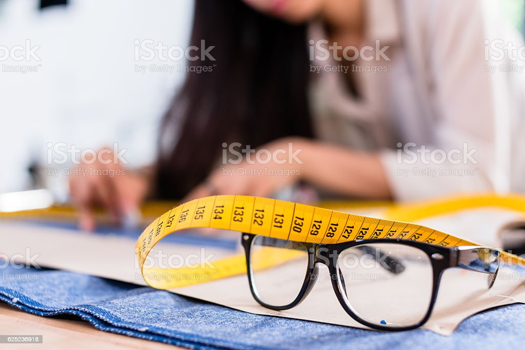 Detail of pattern, tape rule and glasses in fashion studio stock photo