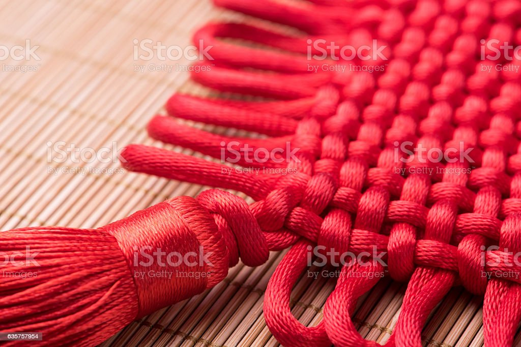 Detail of red Chinese knot on bamboo mat stock photo