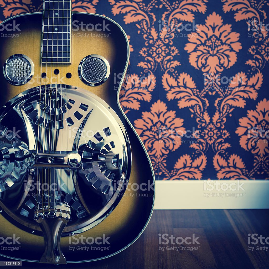 Detail of resonator guitar and damask wall stock photo
