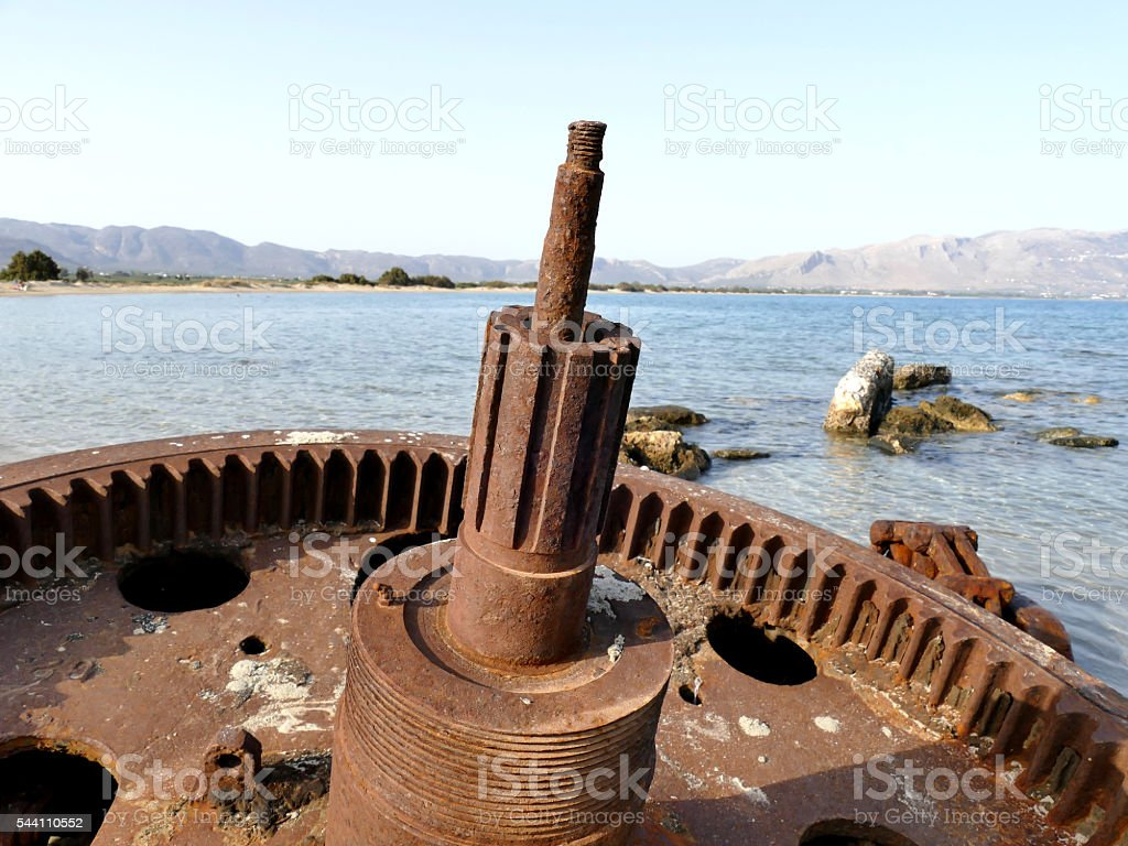 Detail of rusted cogwheel of old ship stranded on beach stock photo