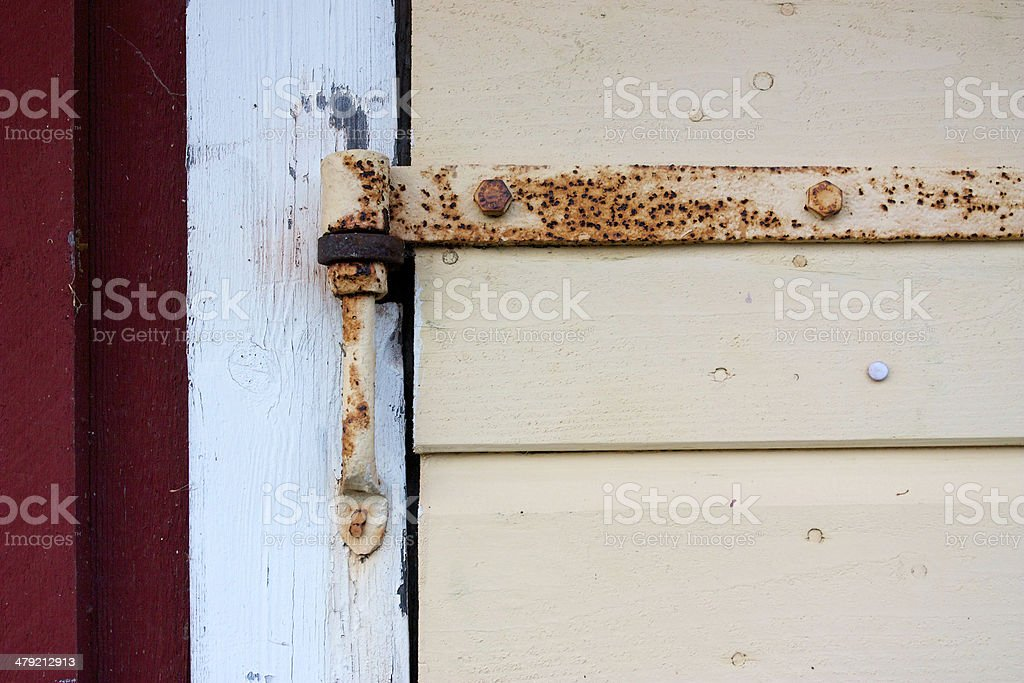 Detail of rusted hinge on wooden door stock photo