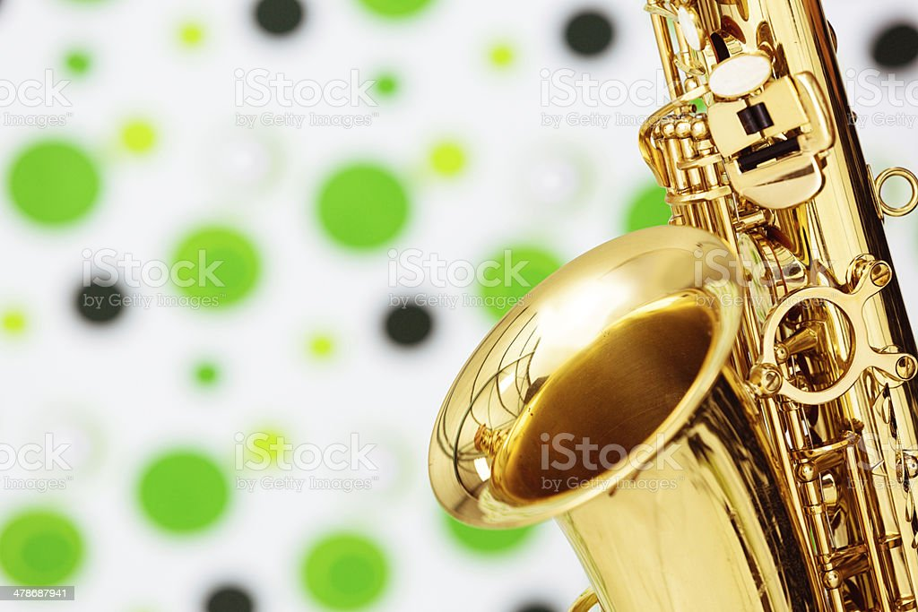 Detail of saxophone against out-of-focus polka-dotted background royalty-free stock photo