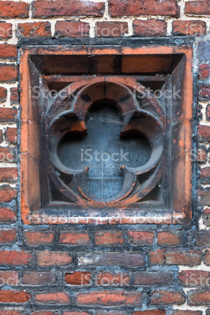 Detail of Tudor architecture exterior rose-shaped wall window slit stock photo