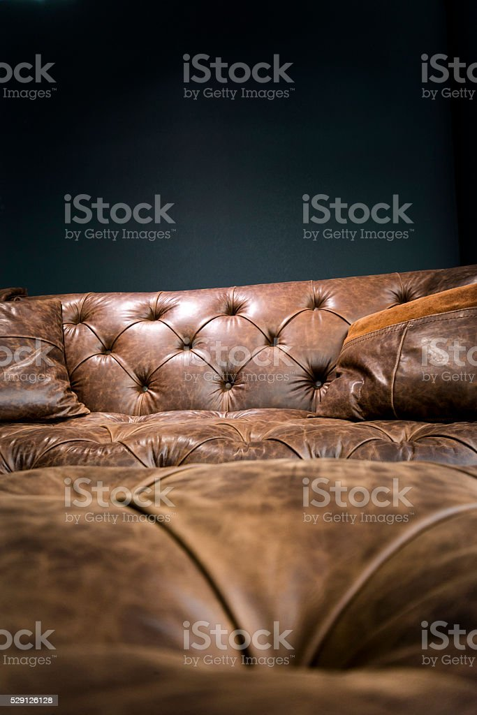 Detail of Vintage Brown Leather Sofa under Black Empty Wall stock photo