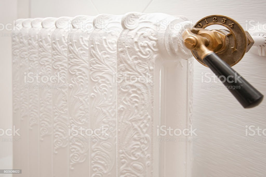Detail of vintage white restored radiator with handle. stock photo