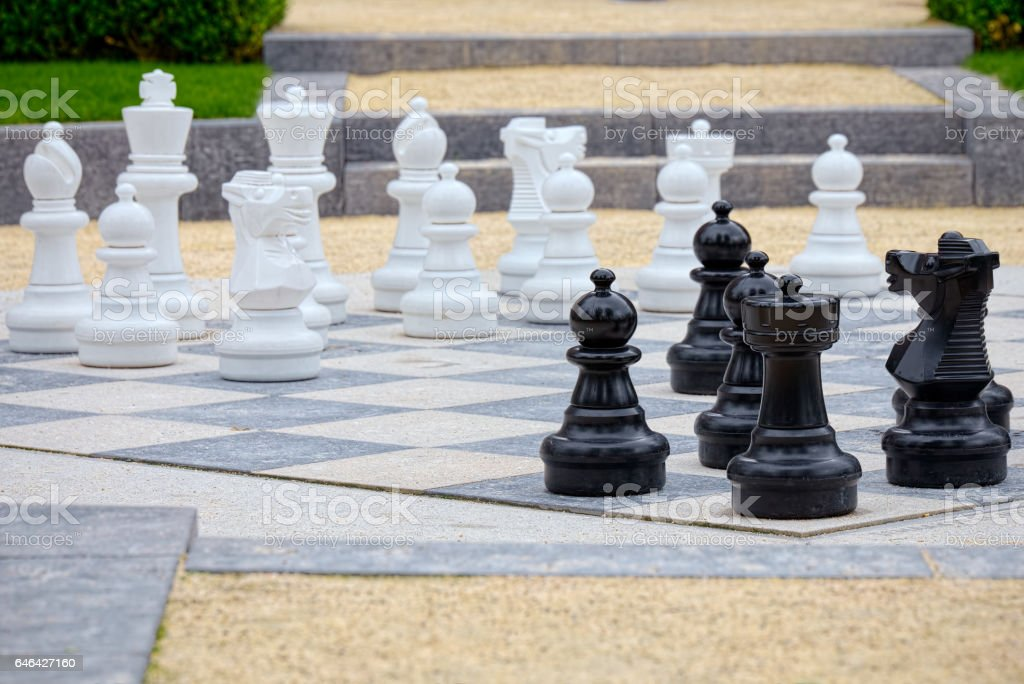 Detail of whites and blacks pieces of an outdoor chess stock photo