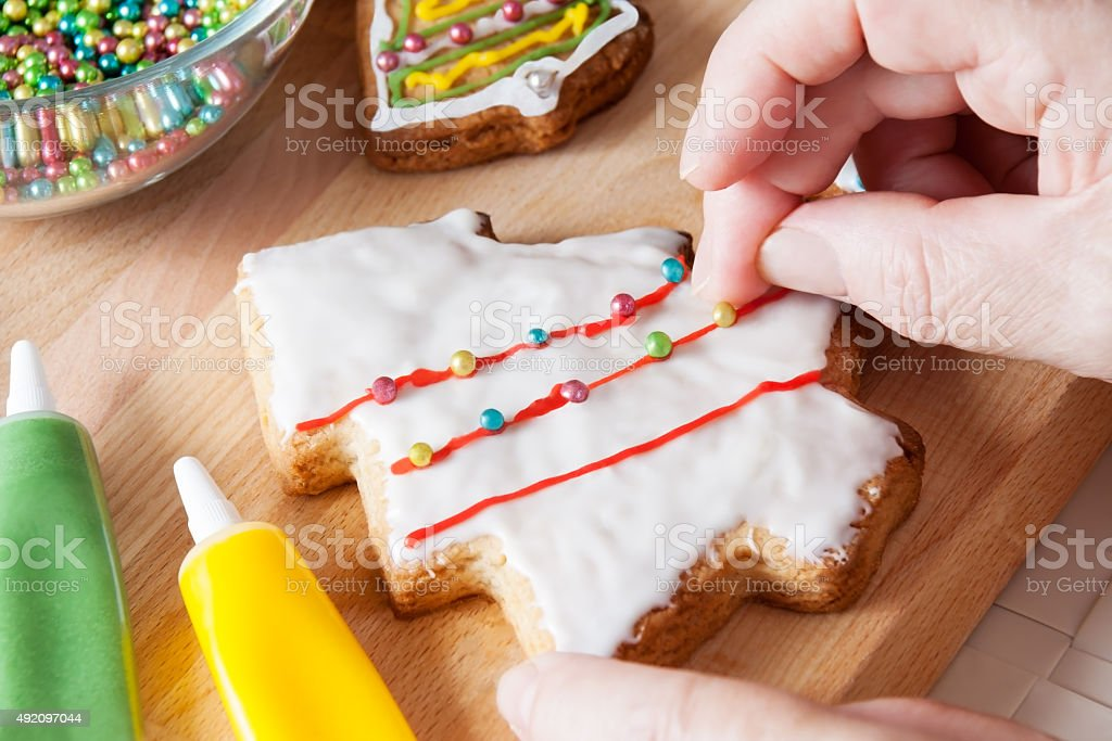 Detail of woman's hand  decorating Christmas cookie. Selective focus stock photo