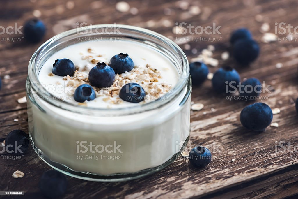 Detail of Yogurt with Fresh Blueberries on Woden Table stock photo