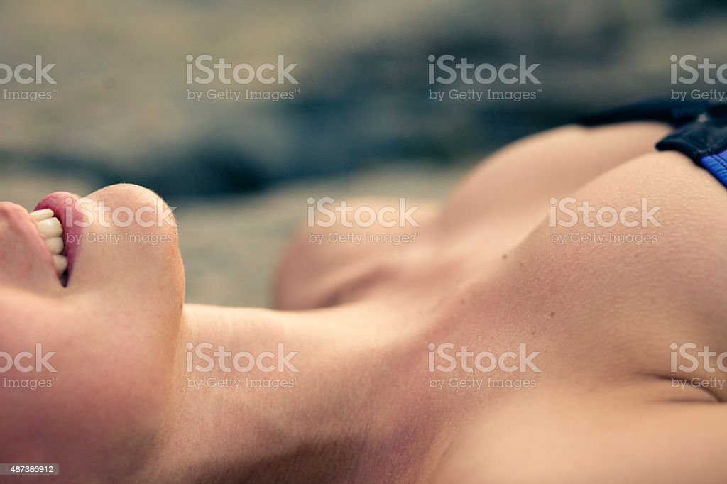 detail shot - woman with beautiful smile and breast tanning stock photo