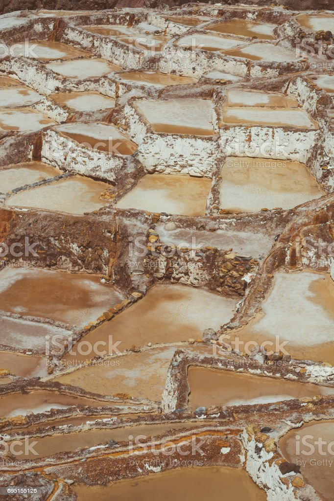 Detail view of the Maras salt ponds located in Peru's Sacred Valley. Vertical image. stock photo