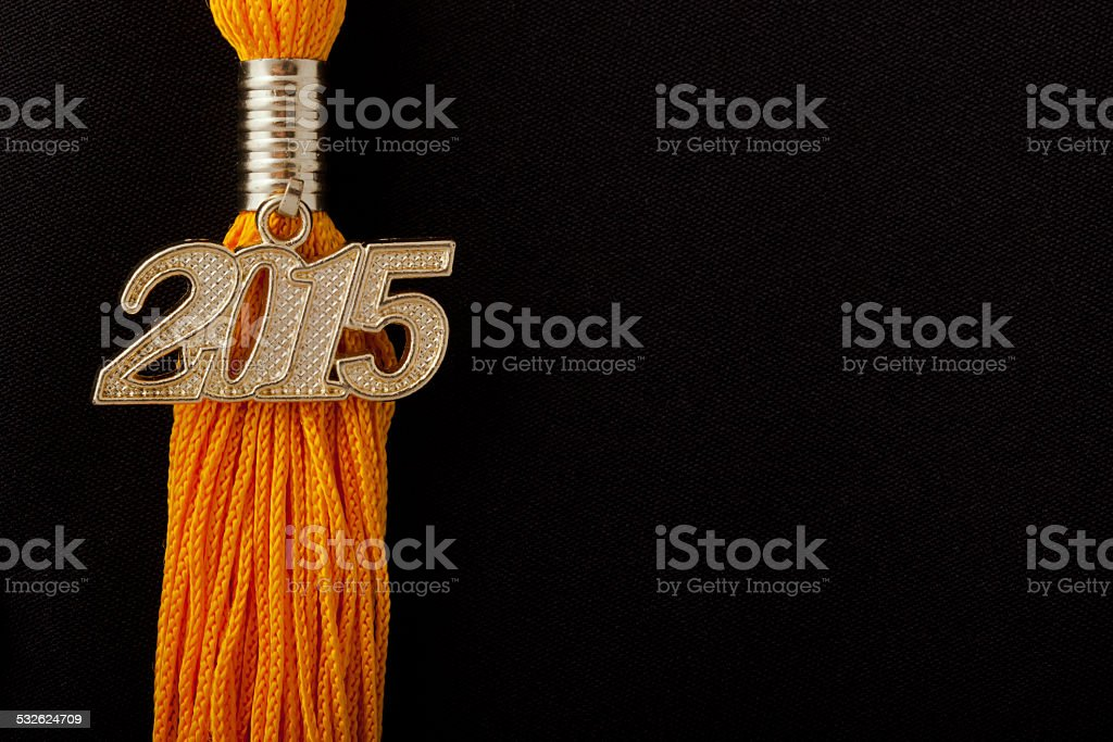 Detail view of yellow class of 2015 graduation tassel. stock photo