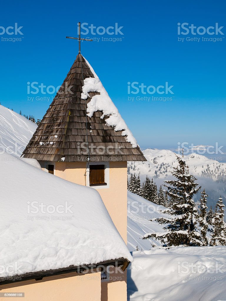 Detailed view of rural mountain church tower with cross on stock photo