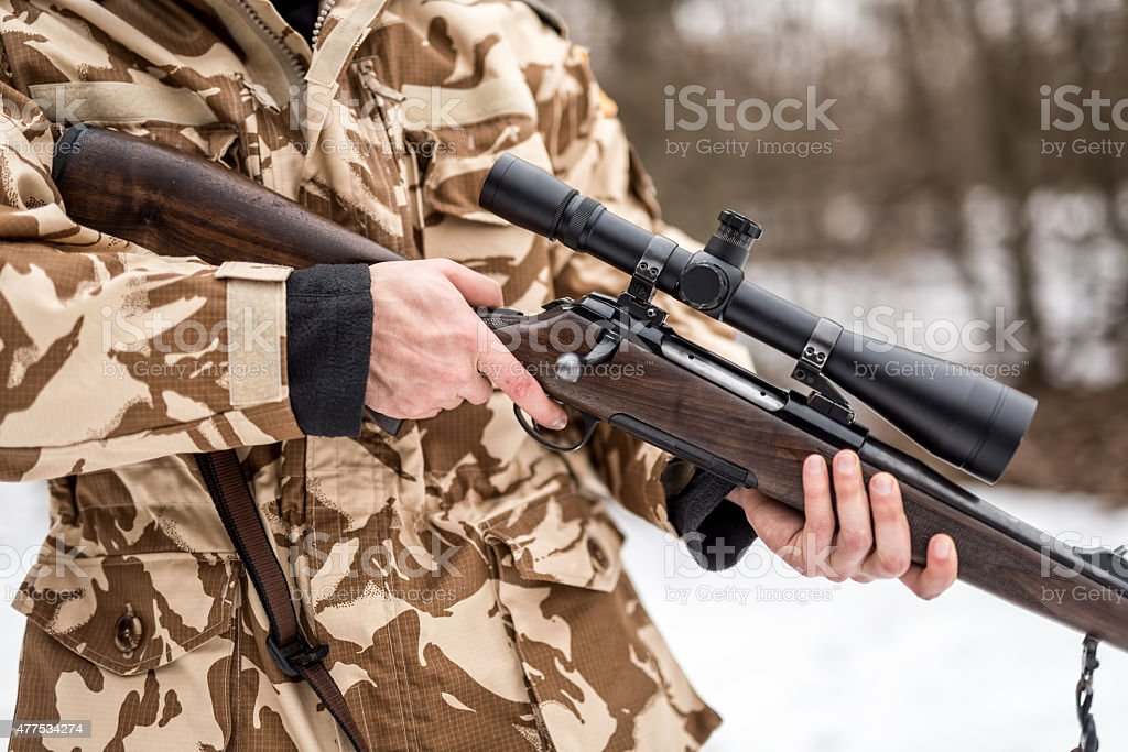 details of a man wearing a camouflage suit holding sniper stock photo