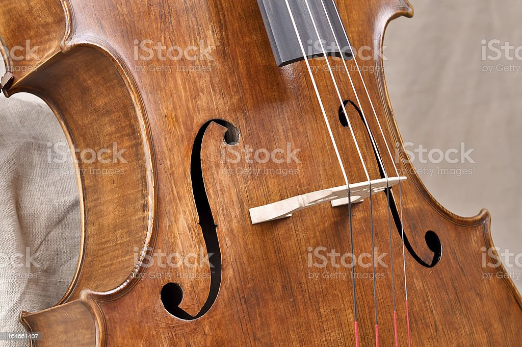 Details of a violoncello on beige background royalty-free stock photo