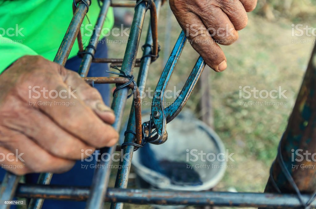 Details of construction worker - hands securing steel bars stock photo