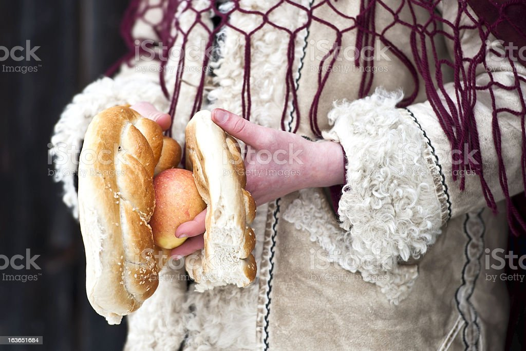 Details of hands holding pretzel and apple. Traditional Romanian wear royalty-free stock photo