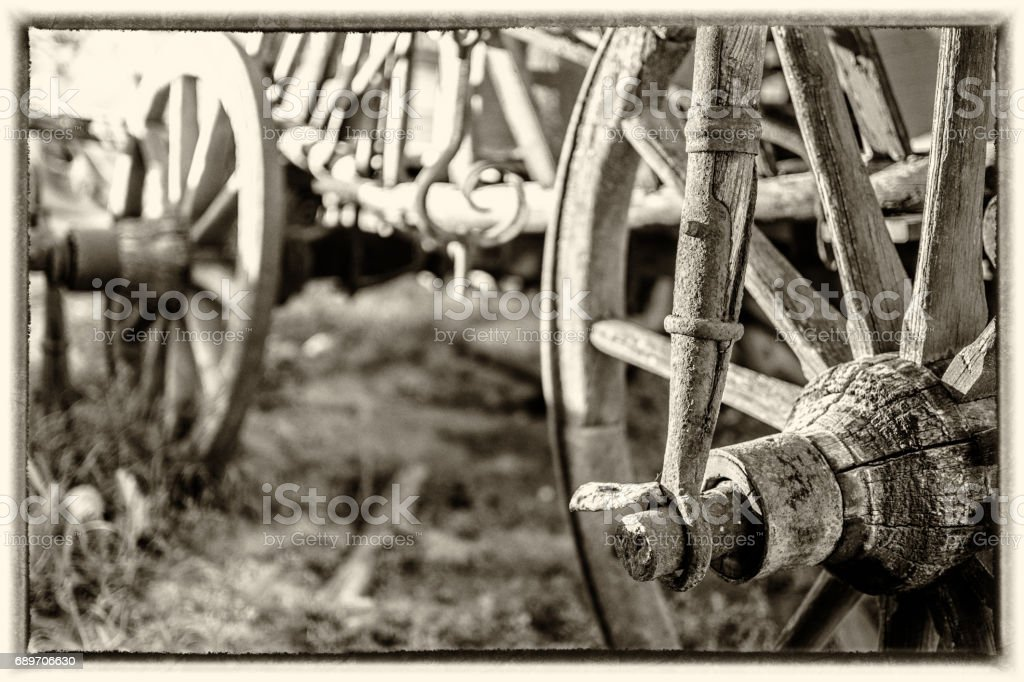 Details of the wooden wheels of an old cart, at sepia style. stock photo