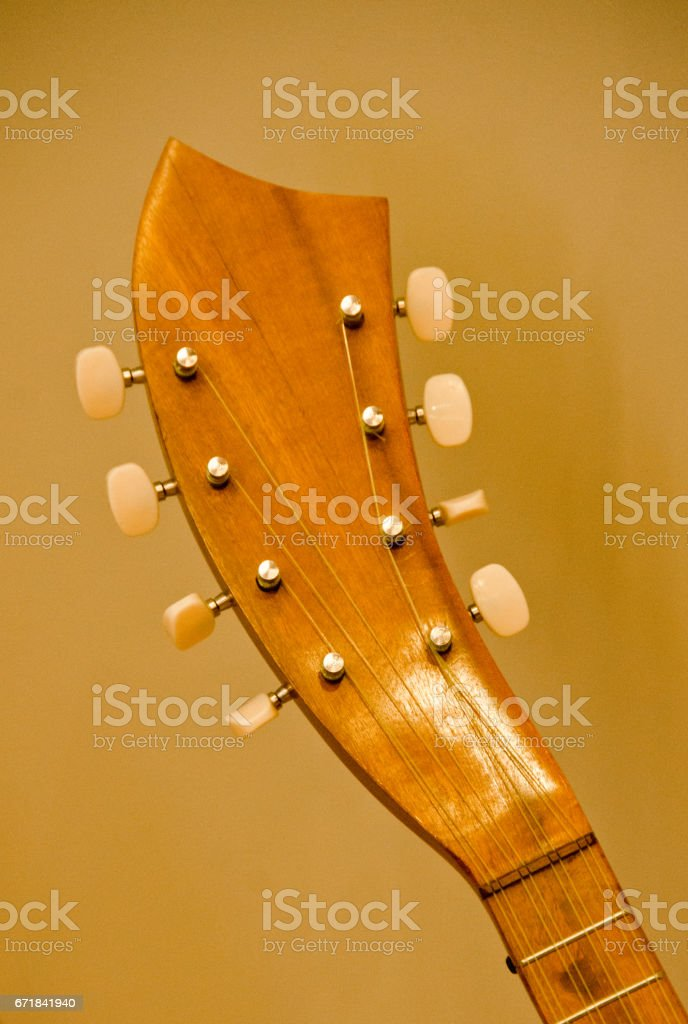 Details of unusual headstock of a mandolin with lit background stock photo