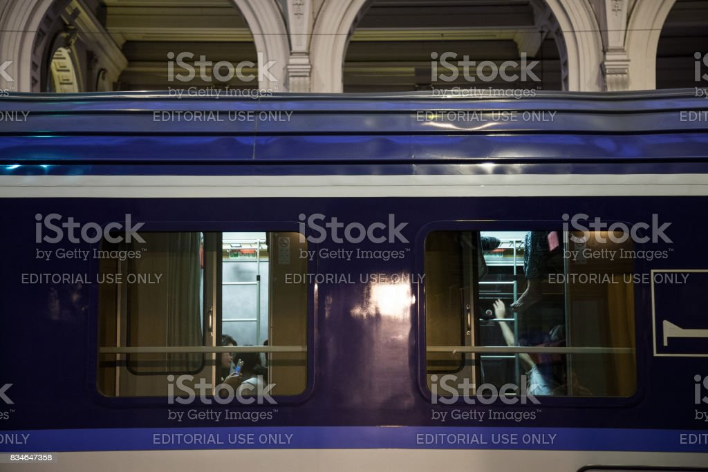 Details on windows of an overnight train ready for departure with people on beds in the interior of the train stock photo