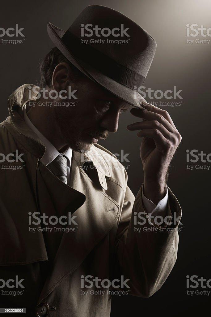 Detective adjusting his hat stock photo