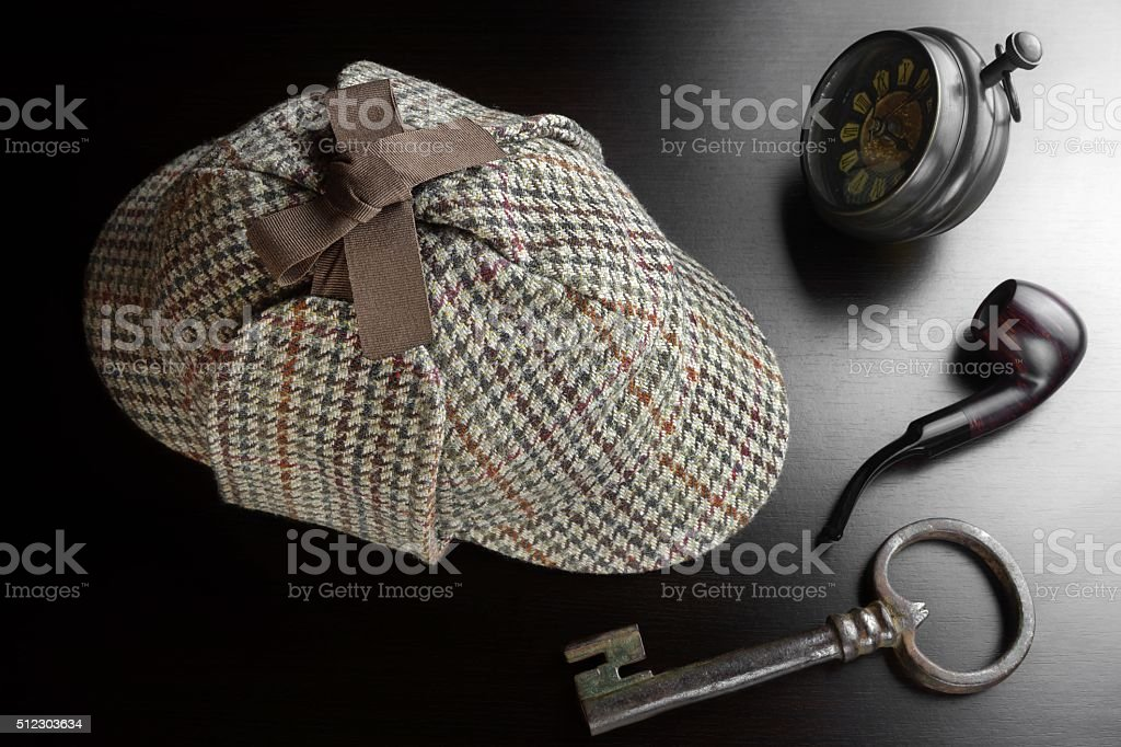 Sherlock Deerstalker Hat,  Key, Clock,Smoking Pipe On Black Tabl stock photo