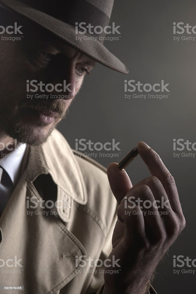 Detective holding a bullet stock photo