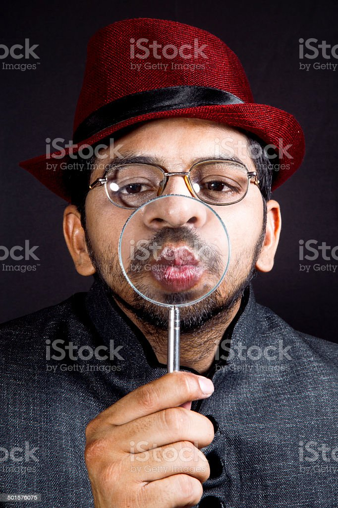Detective holding magnifying glass up to his lips royalty-free stock photo