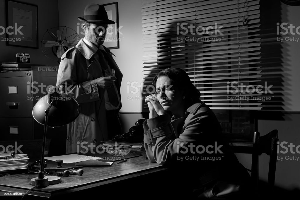 Detective interviewing a young pensive woman in his office stock photo
