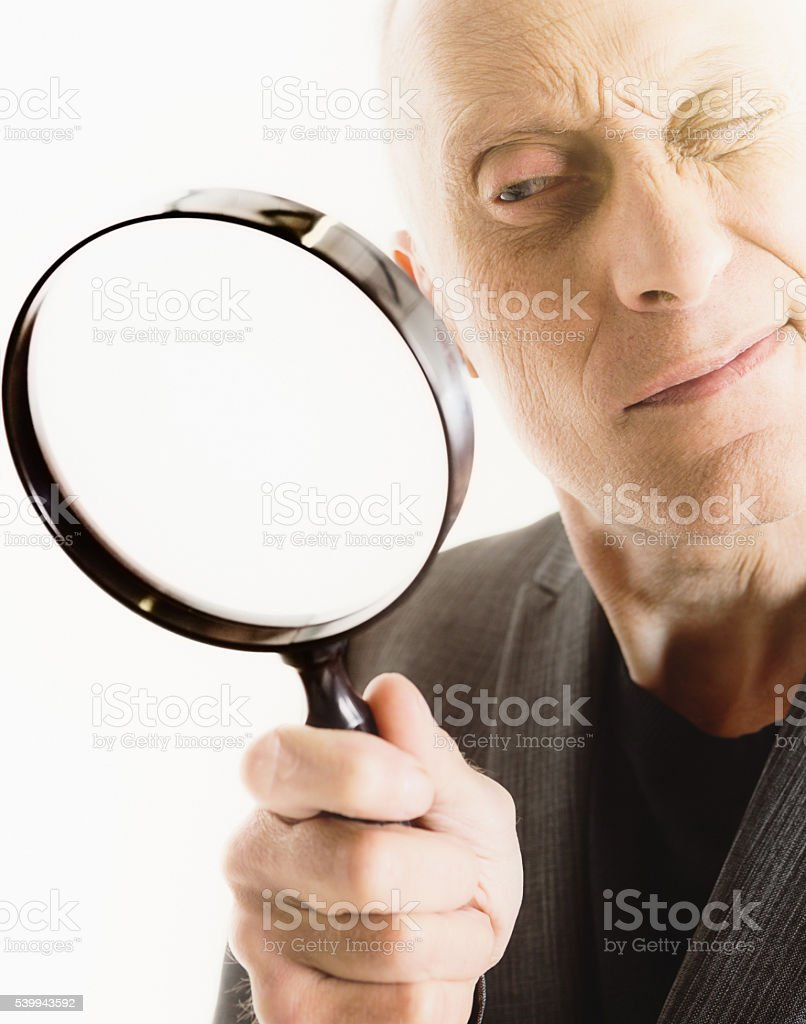 Detective, mature man, spying, snooping, examining, magnifying glass, eyesight, curious stock photo