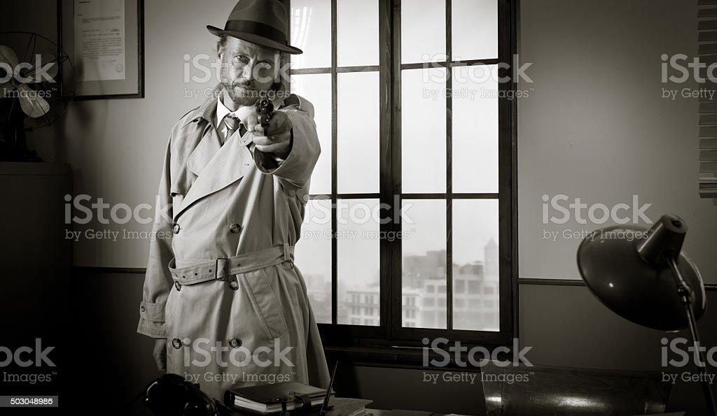 Detective pointing a gun stock photo