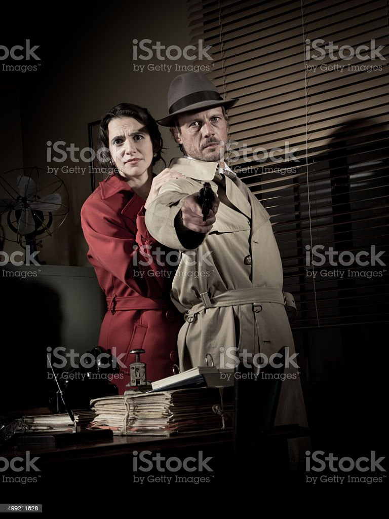 Detective protecting a young woman pointing a gun stock photo