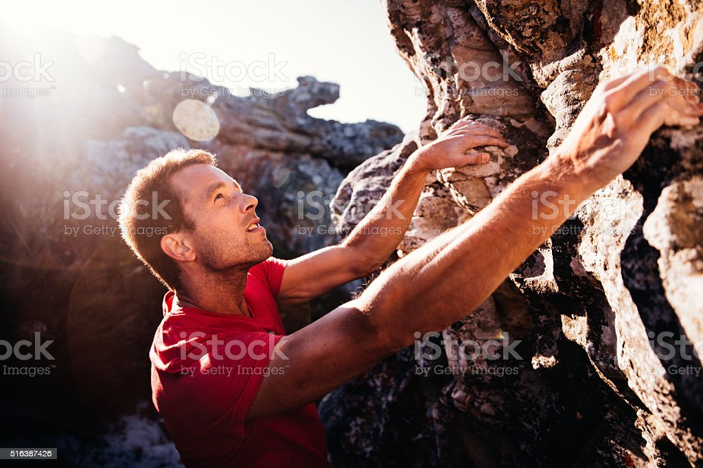 Determination in rock climbing man's face during ascent of mountain stock photo