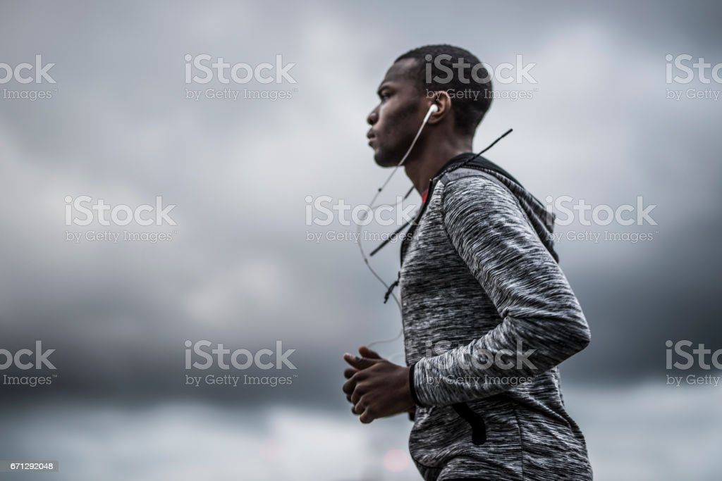 African-American man running outdoors in the city. He is focused and...