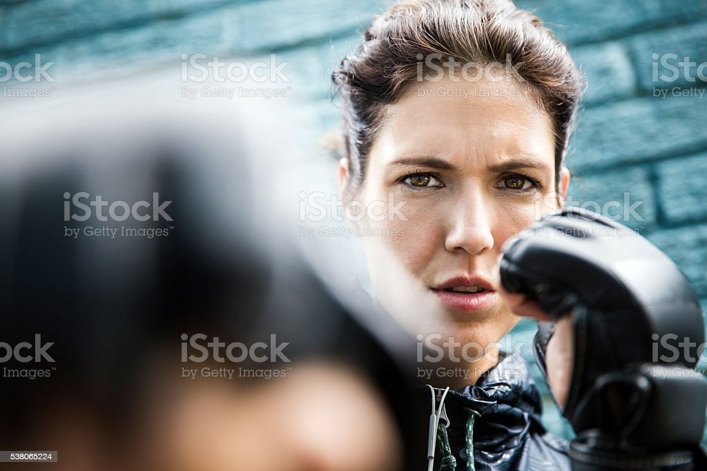 Determined athlete boxing against wall stock photo