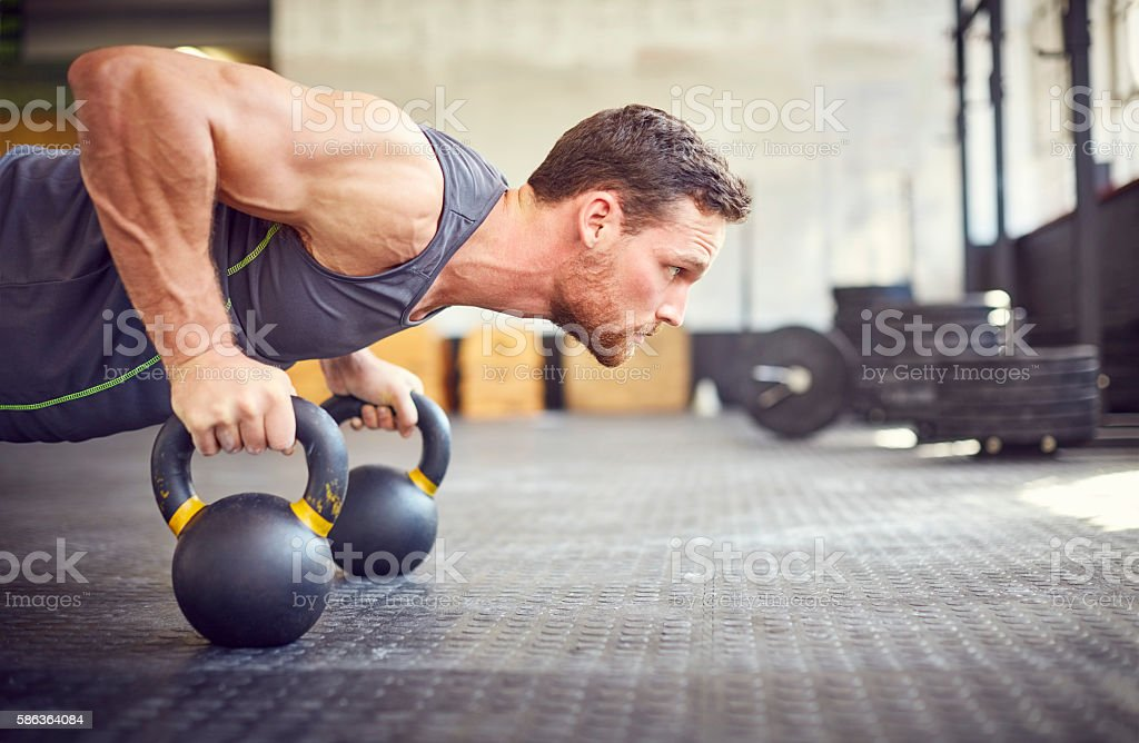 Determined athlete doing push-ups on kettlebells in gym stock photo