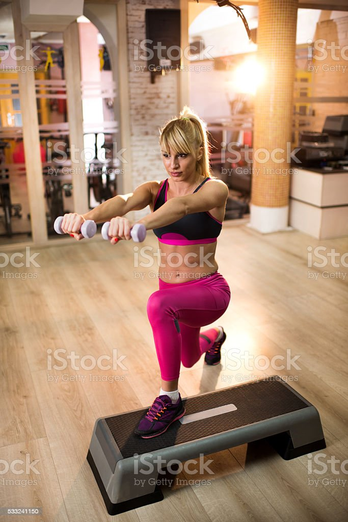 Determined athlete exercising step aerobics with hand weights. stock photo
