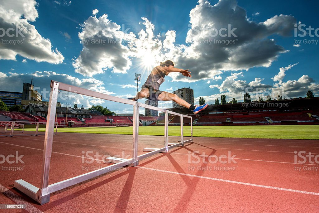 Determined athlete jumping hurdles on a sports race. stock photo