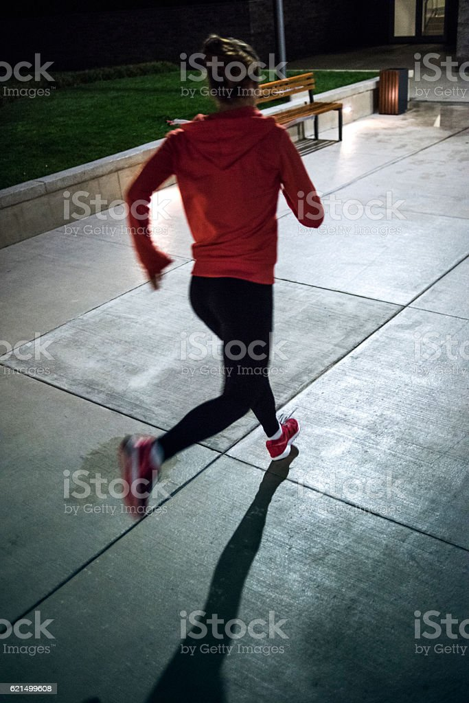 Determined athlete running on a cold night stock photo