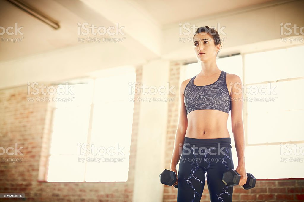 Determined attractive female holding dumbbells while looking awa stock photo