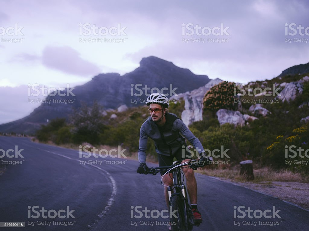 Determined cyclist in recreational pursuit with bicycle on mountain road stock photo