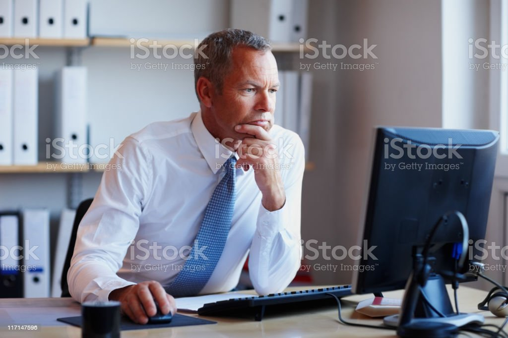 Determined executive working on project looks at computer screen royalty-free stock photo