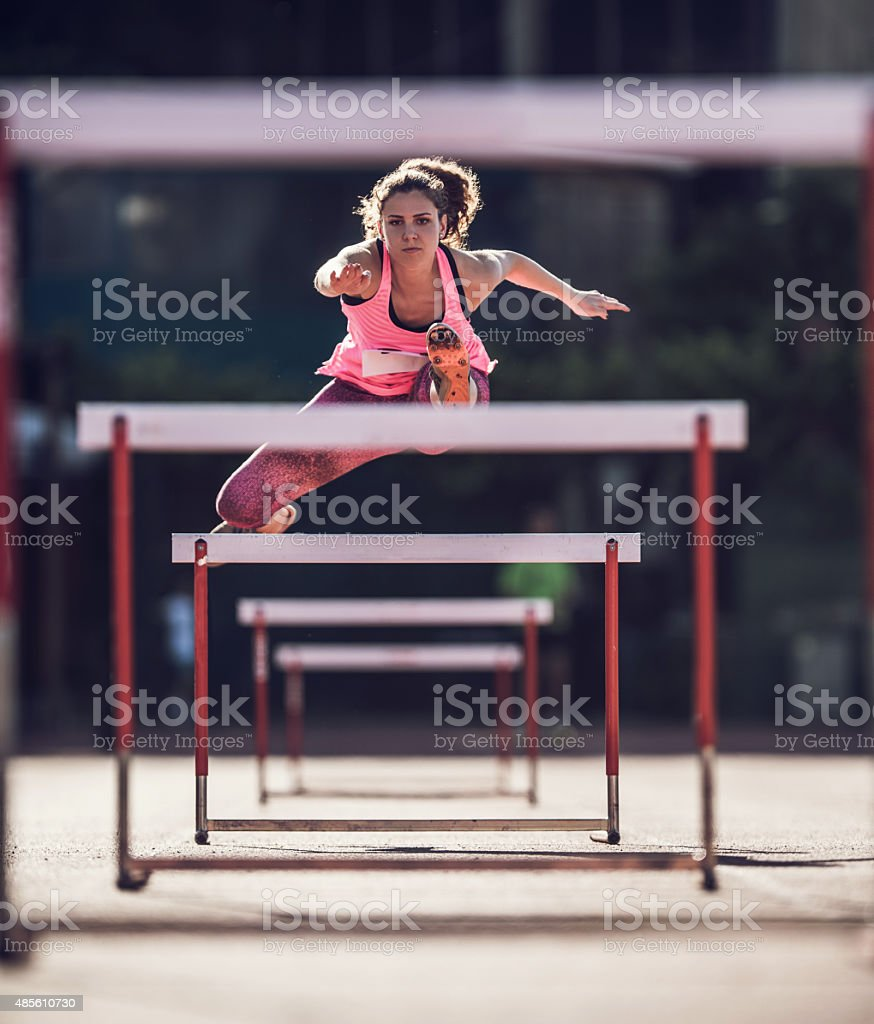Determined female athlete jumping hurdles on a race. stock photo