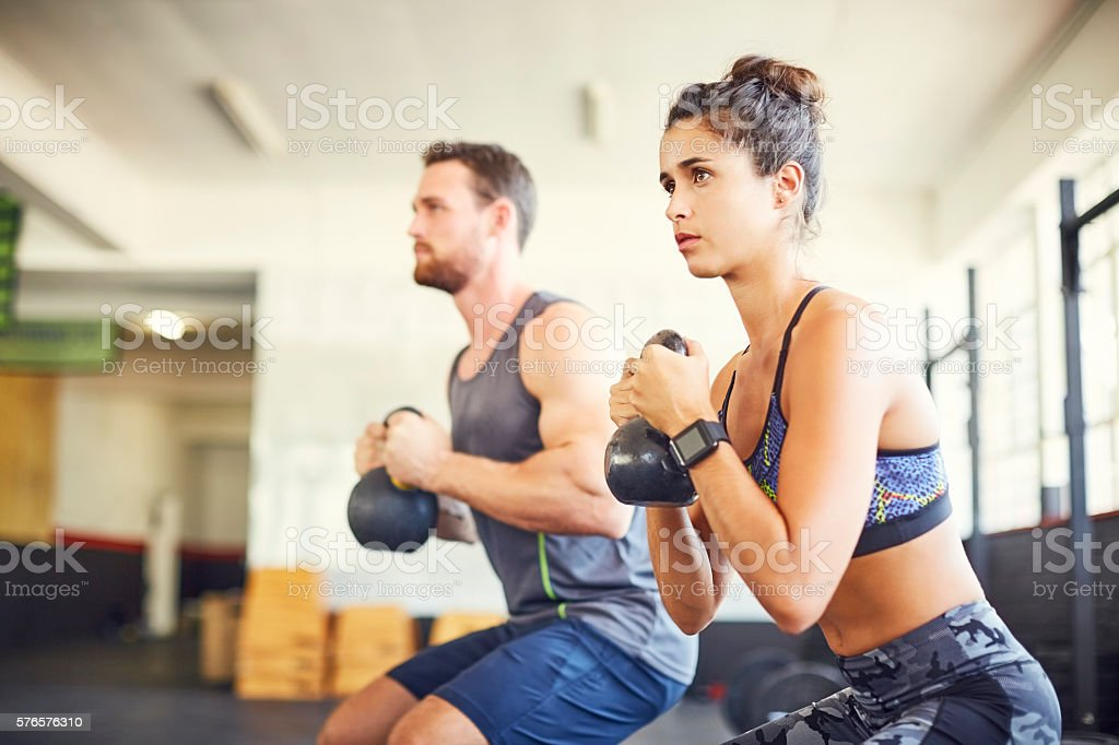 Determined female athlete with instructor exercising in health c stock photo