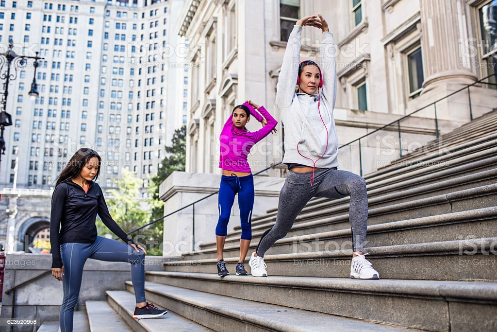Determined female athletes warming up on steps stock photo