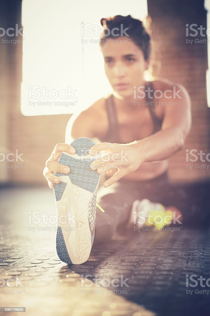 Determined female doing stretching exercise in gym stock photo