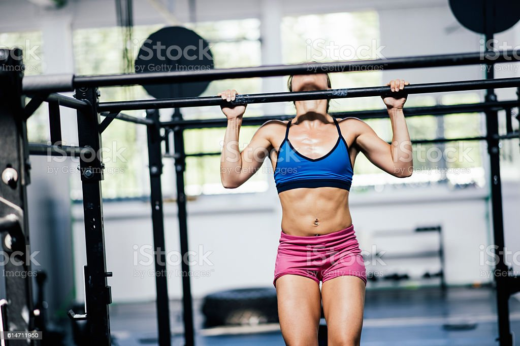 Determined girl doing pull-ups stock photo