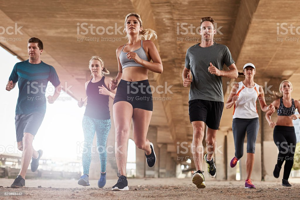 Determined group of young people running in city stock photo