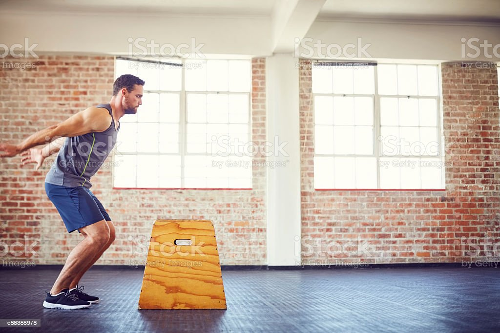Determined male athlete doing box jumping at gym stock photo